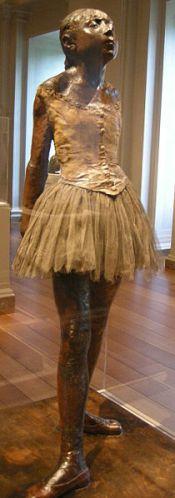 """אדגר דגא, """"רקדנית קטנה בת 14"""" (המקורי), 1878-1881. שלד מתכת, חומר משוח בשעוות דבורים צהובה, שער אנושי משוח בשעווה צהובה, פנים משכבות על שכבות של שעווה צהובה, סרט, לסוטת בד, נעלי סטן משוחות בשעווה ורודה, טוטו מוסלין, חבל, כַּן עץ, 98.9 x 34.7 x  35.2 ס""""מ ללא הכן,  The National Gallery of Art, Washington, via Flicker"""