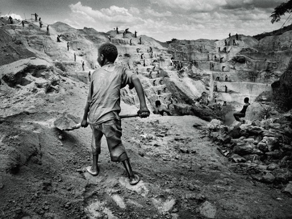 Marcus Bleasdale, ילד במכרה של המיליציות ב-Watsa, צפון מזרח הרפובליקה הדמוקרטית של קונגו. המחצבים של קונגו, ביניהם קולטן, מינרל ממנו מופקת אבקת טנטלום החיונית לייצור רכיבים אלקטרוניים שלנו, הם שמממנים את האלימות הרצחנית במדינה. 2013.  Via National Geographic
