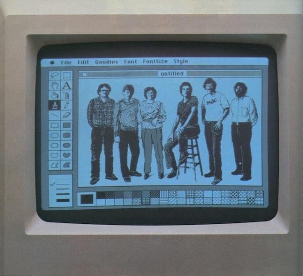 """סטיב ג'ובס מוקף בצוות Mac המקורי עם """"סמלי מצויינות"""" להשראה.  Via Cult of Mac"""