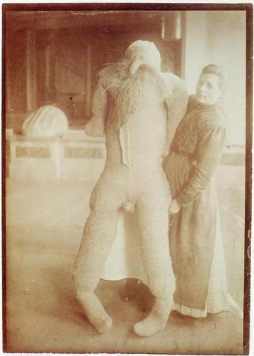 """Katharina Detzel (1872-1941), האמנית עם בובת גבר בגודל טבעי, תפורה מארג המזרן שלה, ממולא בקש המזרן, עטור בזקן קש,  The Prinzhorn Collection, Die Heidelberger Universitäts-Psychiatrie pathologisiert Kunst, via Flashbak Katharina Detzel (1872-1941), האמנית עם בובת גבר בגודל טבעי, תפורה מארג המזרן שלה, ממולאת בקש המזרן, עטור בזקן קש,  The Prinzhorn Collection, Die Heidelberger Universitäts-Psychiatrie pathologisiert Kunst, via Flashbak קתרינה דטצל נחבשה במוסד פסיכיאטרי ב-1907, זאת לאחר שנחשדה בחבלה במסילת הרכבת במסגרת מחאה פוליטית. נשים רבות נכלאו בתקופה ההיא בבתי משוגעים אחרי שהובחנו כמרדניות כרוניות, גם משום שבמעשיהן הפורעים את הגיון התקופה נחשבו למטורפות וגם ככלי דיכוי מתחסד. טרם שהנאצים רצחו אותה במסגרת תכנית האותנזיה שלהם (תוכנית T4( כתבה דטצל מחזה, יזמה ללא הצלחה הקמת בית מחסה לתינוקות, הקימה מחאה נגד אופן הטיפול בחוסים וגם יצרה דמויות מיניאטורה מלחם לעוס. דמות הגבר שיצרה מהמזרן שלה במוסד שימשה אותה לחבטות שעה שכעסה וכבן זוג לריקוד כשלבה היה טוב עליה. ככלל, שימש לה  אותו """"בּוּבּ"""" סרוגייט ליחסי אנוש שנשללו ממנה. אבל אם נתעקש להתבונן היטב ביציר כפֵּיה של דטצל, נוכל להבחין כי היא לא זנחה כלל וכלל את המרד והמחאה נגד השלטון המינני האבסולוטי, מחאה הנועצת את מבטה האירוני בכזבי הידוע-לכל. מוזרותו המגוחכת של היצור האהוב-שנוא שלה נבטת אלינו כעַין שלישית במרכז גופו. זוהי נקודת מוקד שאיננה, בסופו של דבר, שום דבר חוץ מחור וחור בלבד, קטנטן אמנם כחוד סיכה, אבל כזה שמצליח לחורר את כל תורת """"החסר"""" הלקאניאנית."""