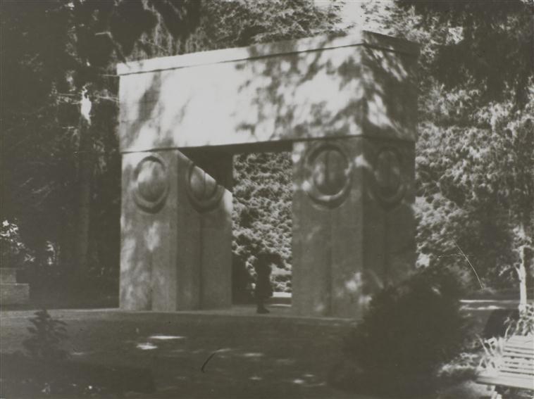 constantin-brancusi-porte-du-baiser-de-trois-quarts-cote-parc-avec-effet-de-lumiere-contrastee-a-travers-le-feuillage-des-arbres-1938-1938-centre-pompido